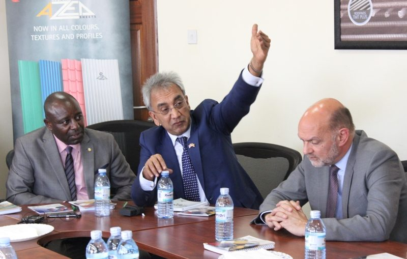 Lord Popat responds to media inquiries during his visit of Roofings Namanve plant as British High Commissioner Peter West and Stuart Mwesigwa from Roofings listen on