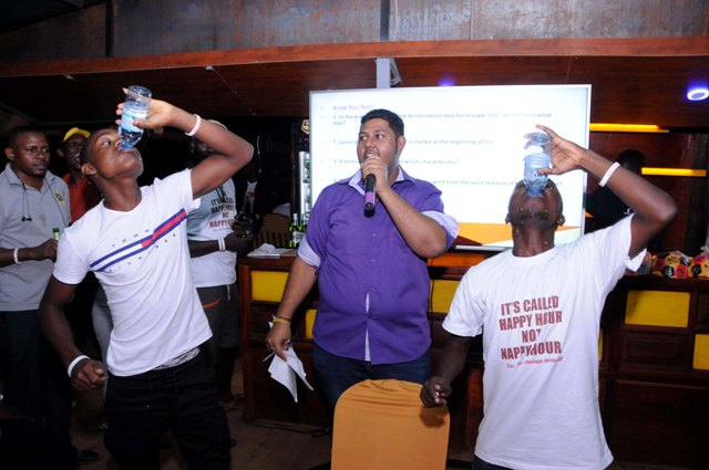 Participants in the Smart Drinking quiz compete in water challenge during the quiz. Back is Jayant Maru the quiz master.