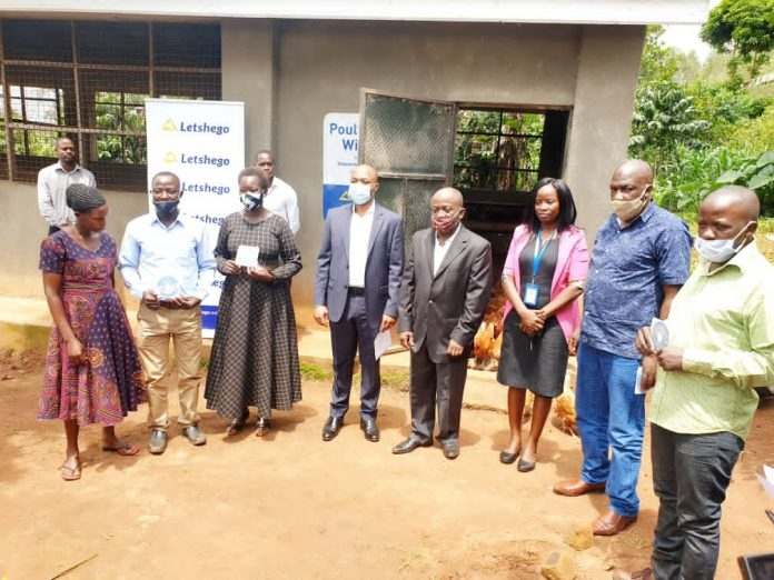 Regional farmers take a group photo with Giles Aijukwe CEO Letshego and Letshego board director Peter Masaba (Center) during ILC Poultry project handover in Wakiso district